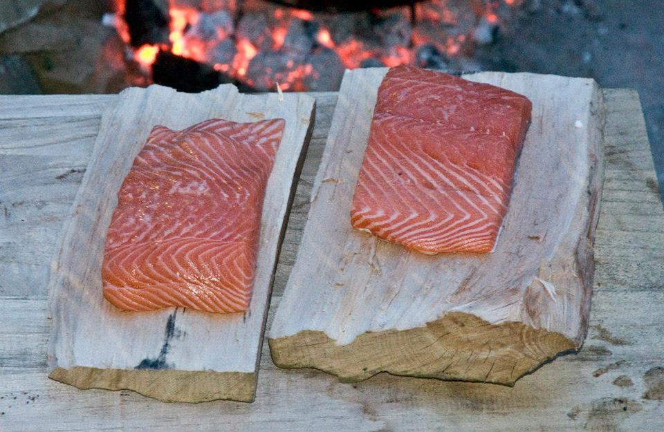 Lachs wird vorbereitet für das Garen am Holzscheit