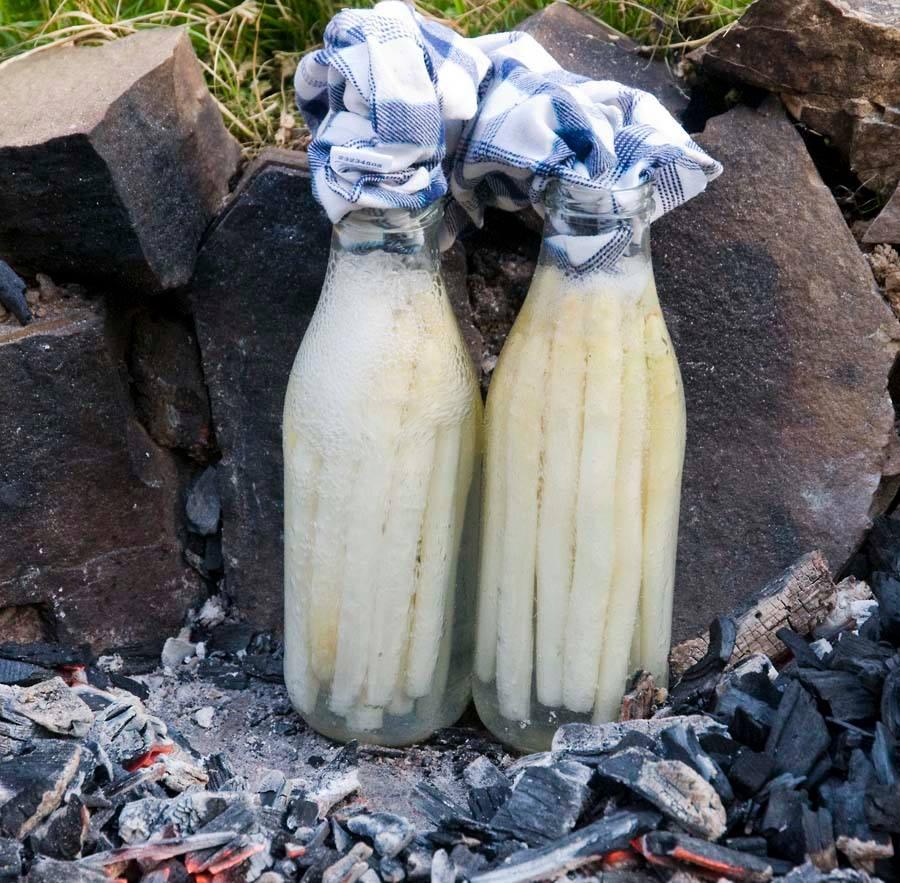 Spargel gart in der Glasflasche am Feuer